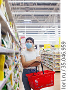 Young woman wearing disposable medical mask shopping in supermarket during coronavirus pneumonia outbreak. Стоковое фото, фотограф Дарья Филимонова / Фотобанк Лори