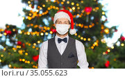 man in protective masks and santa hat on christmas. Стоковое фото, фотограф Syda Productions / Фотобанк Лори
