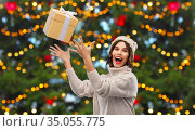 young woman in winter hat catching gift box. Стоковое фото, фотограф Syda Productions / Фотобанк Лори