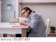 Young male student preparing for exam at home. Стоковое фото, фотограф Elnur / Фотобанк Лори