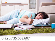 Young male student being tired preparing for exams at home. Стоковое фото, фотограф Elnur / Фотобанк Лори