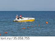 """Мужчины отплывают от пляжа """"Барабулька"""" на водном велосипеде в Чёрное море, Крым. Редакционное фото, фотограф Николай Мухорин / Фотобанк Лори"""