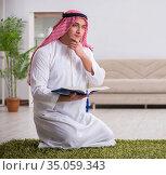 Arab man praying at home. Стоковое фото, фотограф Elnur / Фотобанк Лори