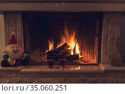 A large stone fireplace with burning wood and two glasses of liquor on Christmas evening. Стоковое фото, фотограф Татьяна Ляпи / Фотобанк Лори