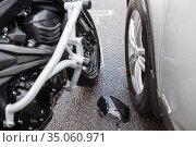 Motorcycle with engine bars hit a car at the road, postcrash investigation of accident, close-up view. Стоковое фото, фотограф Кекяляйнен Андрей / Фотобанк Лори