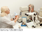 Doctor ophthalmologist checks the eyesight of an senior man patient. Стоковое фото, фотограф Юлия Бабкина / Фотобанк Лори