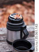 A metal steel thermos and a cup with a hot drink, tea, coffee stands on a table on a wooden background in nature in a hike on a halt in autumn in the forest. Стоковое фото, фотограф Светлана Евграфова / Фотобанк Лори