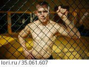 Male MMA fighter standing at the grid in a cage. Стоковое фото, фотограф Tryapitsyn Sergiy / Фотобанк Лори