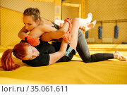 Female MMA fighter performs painful hand grab. Стоковое фото, фотограф Tryapitsyn Sergiy / Фотобанк Лори