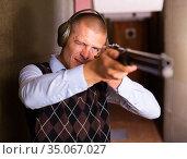 Focused man aiming shotgun at target in shooting range. Стоковое фото, фотограф Яков Филимонов / Фотобанк Лори