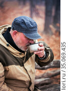 Active lifestyle. A man tourist 40 years old drinks a hot drink coffee tea from a thermos mug in the cold autumn outdoors outdoors in the woods at a halt in a hike on a walk in the fresh air. Стоковое фото, фотограф Светлана Евграфова / Фотобанк Лори