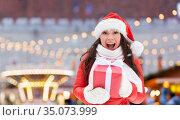 happy woman in santa hat with chrismas gift. Стоковое фото, фотограф Syda Productions / Фотобанк Лори