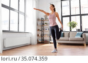 smiling young woman stretching leg at home. Стоковое фото, фотограф Syda Productions / Фотобанк Лори