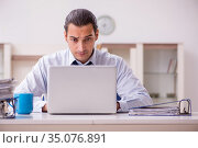 Young male employee working from home in pandemic concept. Стоковое фото, фотограф Elnur / Фотобанк Лори