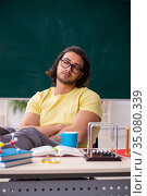Young male student physicist preparing for exams in the classroo. Стоковое фото, фотограф Elnur / Фотобанк Лори