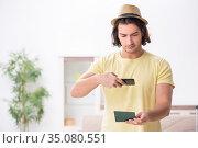 Young man holding passport preparing for summer trip. Стоковое фото, фотограф Elnur / Фотобанк Лори