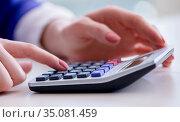 Hands working on accounting calculator calculating profit. Стоковое фото, фотограф Elnur / Фотобанк Лори