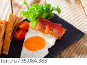 Cooked eggs with bacon, toasted bread, tomatoes and lettuce at plate on table. Стоковое фото, фотограф Яков Филимонов / Фотобанк Лори