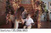 Mom and son sit on a wooden. Стоковое видео, видеограф Потийко Сергей / Фотобанк Лори