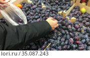 Human hand taking ripe plums in plastic package from a supermarket stall, close up view. Стоковое видео, видеограф Кекяляйнен Андрей / Фотобанк Лори