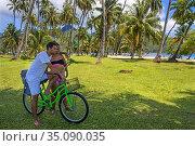 Local teens couple with a bicycle, kissing in Moorea, Cook's Capitan... Редакционное фото, фотограф Sergi Reboredo / age Fotostock / Фотобанк Лори