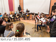 Classical music concert for parents is in Russian children academy of music. Boys and girls with adults play quitar together (2020 год). Редакционное фото, фотограф Кекяляйнен Андрей / Фотобанк Лори