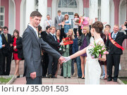 Newlywed couple with members of the wedding stand on stairs of palace. The end of registration with guests congratulations. Man looking at camera (2010 год). Редакционное фото, фотограф Кекяляйнен Андрей / Фотобанк Лори