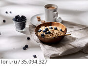 oatmeal with blueberries, spoon and cup of coffee. Стоковое фото, фотограф Syda Productions / Фотобанк Лори