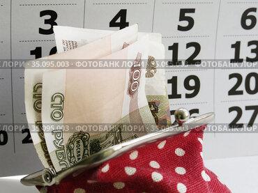 Красный кошелек с купюрами на фоне календаря
