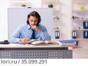 Young businessman student studying at workplace. Стоковое фото, фотограф Elnur / Фотобанк Лори