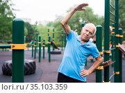 mature cheerful pensioner man doing physical exercises on sports equipped playground. Стоковое фото, фотограф Татьяна Яцевич / Фотобанк Лори