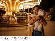 Woman with soft toy near the carousel in park. Стоковое фото, фотограф Tryapitsyn Sergiy / Фотобанк Лори