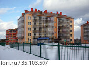 A new residential brick apartment building with glazed balconies stands behind a fence, among snowdrifts in the village of Tayozhny, Krasnoyarsk Territory. Russia. (2020 год). Стоковое фото, фотограф Светлана Попова / Фотобанк Лори