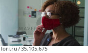 Thoughtful african american woman wearing face mask with hand on chin at modern office. Стоковое видео, агентство Wavebreak Media / Фотобанк Лори