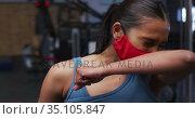Fit caucasian woman wearing face mask sneezing on her elbow in the gym. Стоковое видео, агентство Wavebreak Media / Фотобанк Лори