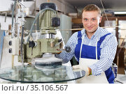 Craftsman working on machine for curved glass faceting. Стоковое фото, фотограф Яков Филимонов / Фотобанк Лори