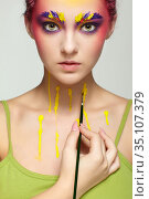Female portrait with unusual face and body art make-up. Woman paints herself with a brush. Стоковое фото, фотограф Serg Zastavkin / Фотобанк Лори