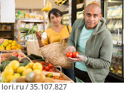 Latin american man looking for fresh tomatoes in supermarket. Стоковое фото, фотограф Яков Филимонов / Фотобанк Лори