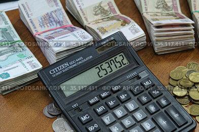 Пачки денег на столе и итоговая сумма на калькуляторе