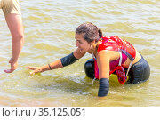 Russia, Samara, June 2019: a man helps a woman athlete get out of a dirty hole in a hero race on a summer sunny day. Редакционное фото, фотограф Акиньшин Владимир / Фотобанк Лори