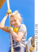 Russia, Samara, June 2019: a beautiful athlete with a smile overcomes with a rope a big dirty hole in the heroes race on a summer sunny day. Text in Russian: race of heroes, platoon. Редакционное фото, фотограф Акиньшин Владимир / Фотобанк Лори