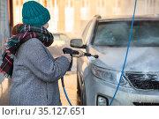 Woman cleaning auto with high pressure water jet at self-service car wash in cold season. Стоковое фото, фотограф Кекяляйнен Андрей / Фотобанк Лори