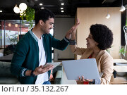 Diverse businessman and businesswoman using laptop and tablet high fiving in office. Стоковое фото, агентство Wavebreak Media / Фотобанк Лори