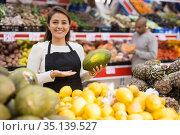 Portrait of positive female merchandiser with melon in hands at supermarket. Стоковое фото, фотограф Яков Филимонов / Фотобанк Лори