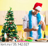 Young chef husband working in kitchen at Christmas eve. Стоковое фото, фотограф Elnur / Фотобанк Лори