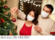 couple in masks decorating christmas tree at home. Стоковое фото, фотограф Syda Productions / Фотобанк Лори