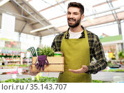 gardener with box of tools at flower shop. Стоковое фото, фотограф Syda Productions / Фотобанк Лори