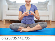 woman with smartphone sitting on mat at home. Стоковое фото, фотограф Syda Productions / Фотобанк Лори