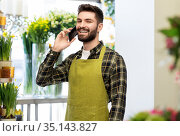 male seller calling on smartphone at flower shop. Стоковое фото, фотограф Syda Productions / Фотобанк Лори