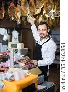 happy male shop assistant using scales for meat in butcher shop. Стоковое фото, фотограф Яков Филимонов / Фотобанк Лори